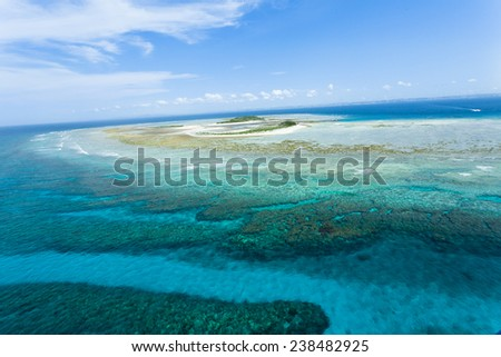 Aerial view of deserted Japanese tropical islands surrounded by coral reefs with clear blue water, Okinawa