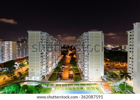 Aerial view of Eunos neighborhood in Singapore at night. The new estate HDB housing complex with outdoor tennis and basketball court, faculties car park, and green garden at the center. - stock photo