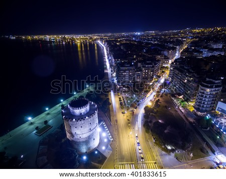 Aerial view of famous White Tower and the city of Thessaloniki at night, Greece. Image taken with action drone camera causing distortion and blur. - stock photo