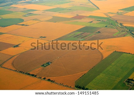 Aerial view of farmland with a mosaic of cultivated land and planted crops   - stock photo