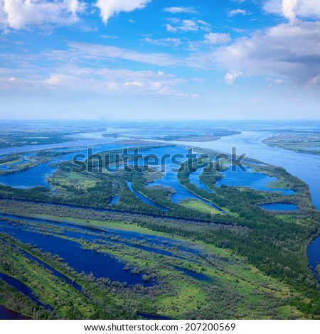 Aerial view of floodland beside great river during summer.