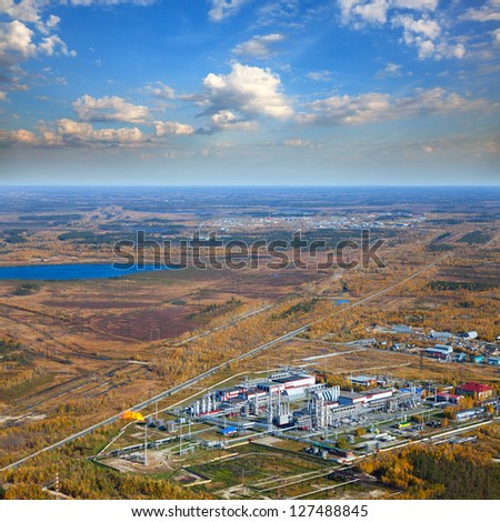 Aerial view of forest plain during a autumn day. It is a top view of the oil field, which is located in forest area. Oil processing plant is located in the foreground. - stock photo