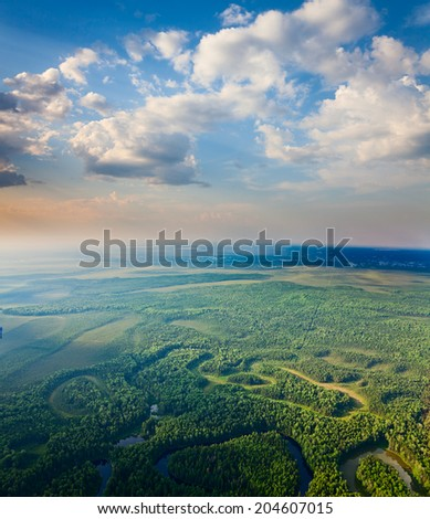 Aerial view of forest river during calm summer evening. - stock photo
