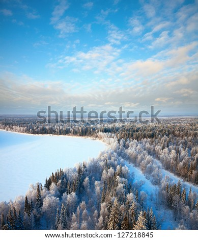 Aerial view of forest which is near river during cold winter day. Magnificent hoarfrost on trees.  A winter forest on rising in a hard frost. - stock photo