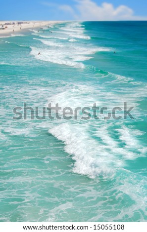 Aerial view of gorgeous ocean with swimmers and beachgoers in distance - stock photo
