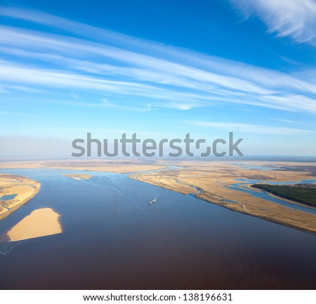 Aerial view of great the river during summer day on background of great white clouds. The ship with barge moves along the river. - stock photo