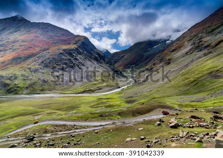 Aerial view of green and rocky landscape of Kargil, with mountain peaks and blue cloudy sky  in background , green valley , Leh, Ladakh, Jammu and Kashmir, India - stock photo