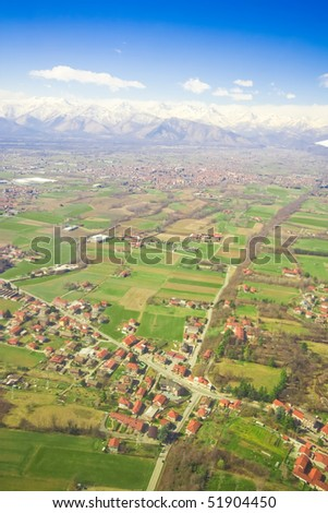 Aerial view of green rural landscape and houses with brown roofs - stock photo
