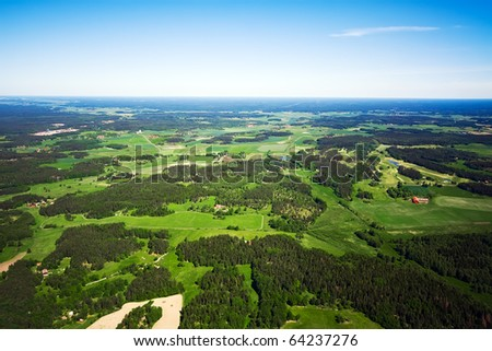 Aerial view of green rural landscape under blue sky - stock photo