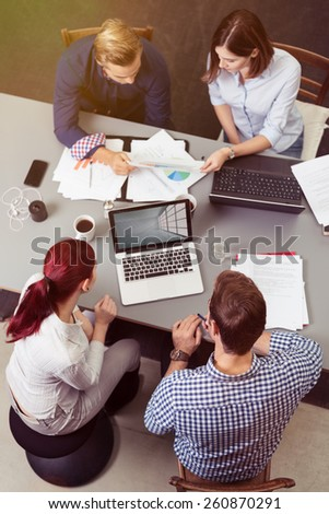 Aerial View of Group of Young Friends Having a Business Meeting at the Table with Laptops and Reports.
