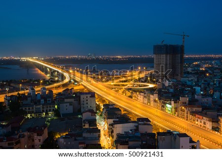 Aerial view of Hanoi cityscape at twilight. Vinh Tuy bridge crossing Red River.