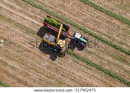 aerial view of harvest field with tractor and combine in Poland - stock photo