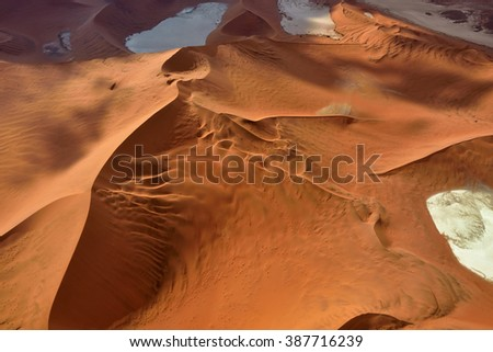 Aerial view of high red dunes, located in the Namib Desert, in the Namib-Naukluft National Park of Namibia - stock photo