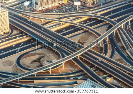 Aerial view of highway junction with little traffic in Dubai, UAE, at sunset. Famous Sheikh Zayed road in Dubai downtown. Transportation and driving concept.