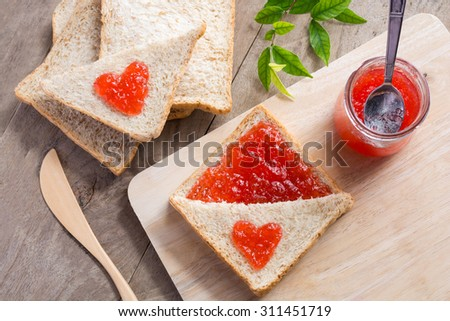 Aerial view of home made bright red strawberry preserves, spread over a slice of white fresh bread. - stock photo