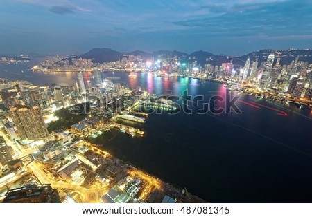Aerial view of Hong Kong & Kowloon (Tsim Sha Tsui) at night with city skyline of crowded skyscrapers by Victoria Harbour & light trails of ships across seaport~ Cityscape of Hong Kong in blue twilight