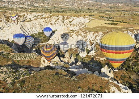 Aerial view of hot air balloons negotiating a path through a limestone gorge in the stunning landscape of rural Cappadocia, Turkey - stock photo