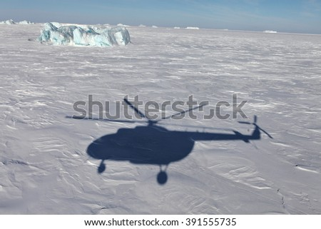 Aerial view of iceberg in frozen Arctic Ocean and helicopter shadow - stock photo