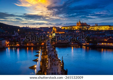 Aerial view of illuminated Prague castle and Charles Bridge with tourist crowd over Vltava river in Prague, Czech Republic. Prague, Czech Republic in the evening - stock photo