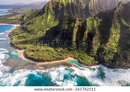 Aerial view of Kee Beach with tall, lush mountains of the Na pali coast and big waves crashing on the reef while on a doors off helicopter tour of Kauai, Hawaii. - stock photo