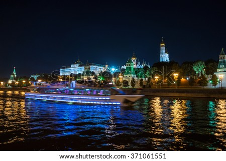 Aerial view of Kremlin at night in Moscow, Russia. Touristic boats moving down the river, car traffic at the road. Popular landmarks in the city - stock photo