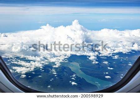 Aerial view of land and rivers covered with clouds - from window of the airplane - stock photo
