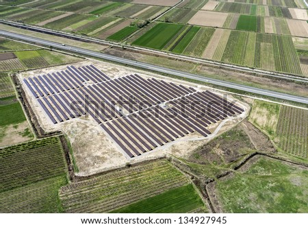 Aerial view of large installation of photovoltaic panels between fields - stock photo