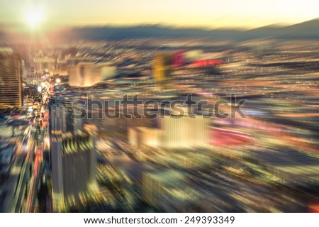 Aerial view of Las Vegas skyline at sunset - Blurred city lights from downtown strip boulevard - Vintage filtered look with radial zoom defocusing - stock photo