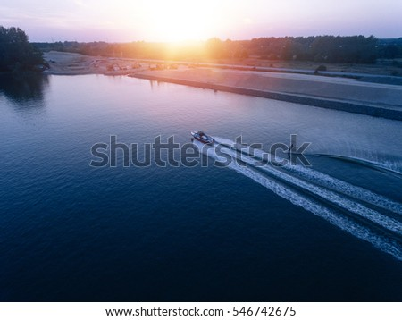 Aerial view of man water skiing on lake behind boat. Man wakeboarding at sunset.