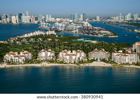 aerial view of miami port entrance and city skyline, with fisher island in foreground, on clear morning, 2016