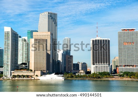 Aerial view of Miami skyscrapers with blue cloudy sky,white yacht docked at Miami downtown