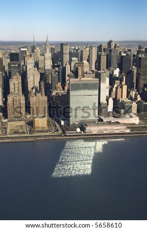 Aerial view of Midtown Manhattan, New York with United Nations Headquarters building reflecting in East River.