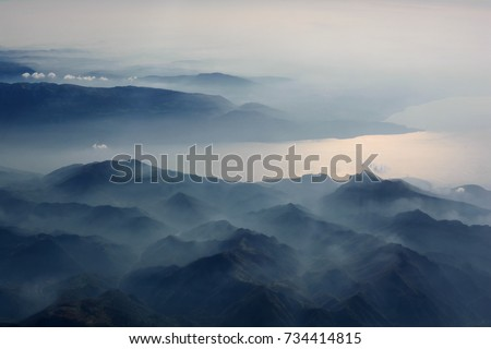 Aerial view of misty mountains, lake and clouds above the mountain peaks, opposite the sunlight, blue tinted