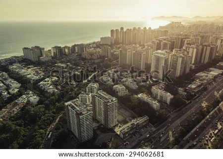 Aerial view of modern Brazilian city at sunset with light leak, Barra da Tijuca - stock photo