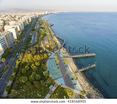 Aerial view of Molos Promenade on the coast of Limassol city in Cyprus. A view of the walk path surrounded by palm trees, pools of water, grass, the Mediterranean sea, piers, rocks and urban skyline. - stock photo