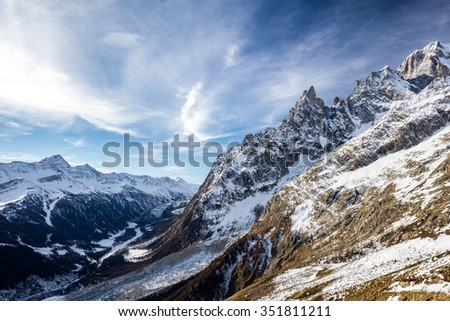 Aerial view of Mont Blanc and Aiguille Noire de Peuterey peak covered of snow, with few cloud in the blue sky.