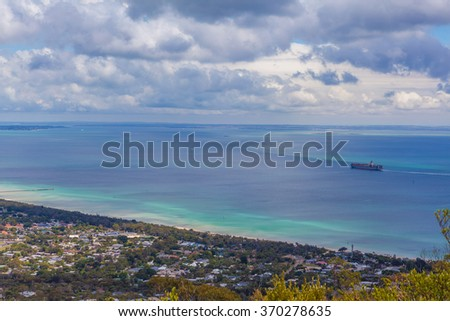 Aerial view of Mornington Peninsula, with cargo ship sailing. Melbourne, Australia. Houses scattered across large bay area - stock photo