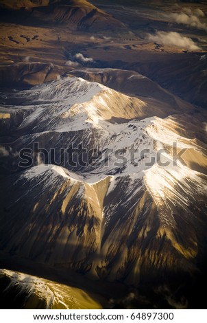 Aerial view of mountain range in New Zealand with snow capped peaks in late afternoon light