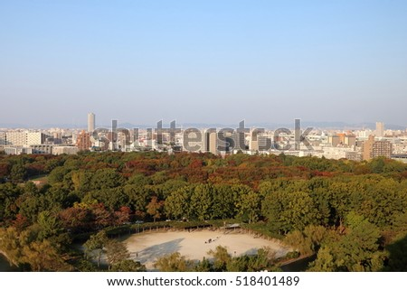 Aerial view of Nagoya City in Aichi Prefecture in Japan at dusk during the golden hour with Autumn foliage visible in the foreground