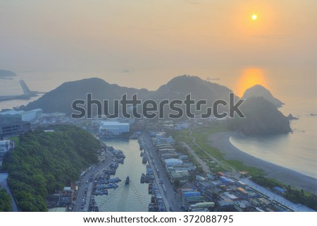 Aerial view of Nanfangao harbor at dawn, a fishing village on northeastern coast of Taipei Taiwan ~ Scenery of misty sunrise reflecting on peaceful sea water by beautiful coastline - stock photo
