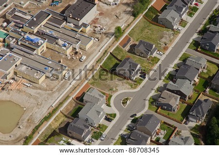 Aerial view of new retail development behind quiet suburban homes - stock photo