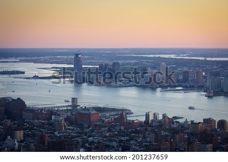 Aerial view of New York and Jersey City, spanning Chelsea, Hudson River and Ellis Island in New York,  and Liberty State Park in New Jersey. The evening light casts its  colors over the Hudson River. - stock photo