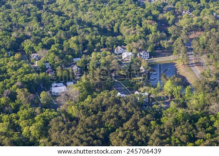 aerial view of nice neighborhood with trees and pond - stock photo