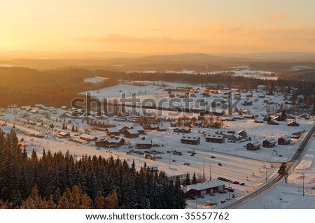 aerial view of nordic village on sunny winter evening - stock photo