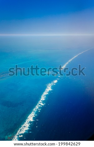 Aerial view of ocean waves breaking over the barrier reef in the Caribbean Sea off the eastern coast of Belize - stock photo