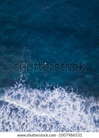 Aerial view of one surfer in the ocean.