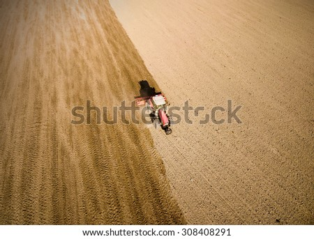 Aerial view of ploughed field with tractor. Industrial background on agricultural theme. - stock photo
