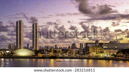 Aerial view of Recife in Pernambuco, Brazil showcasing its mix of historic architecture with buildings dated from the 17th century and modern skyscrapers at sunset. - stock photo