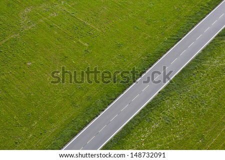 Aerial view of road between green meadow - copy space - stock photo