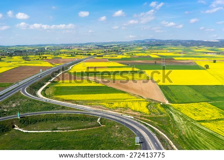 Aerial view of road passing through a rural landscape with blooming rape in northern Greece - stock photo